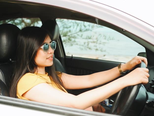 Mulher asiática feliz dirigindo o carro, conceito de viagens.