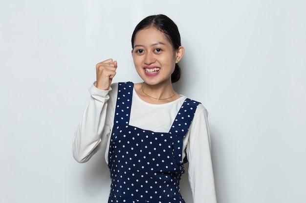 Mulher asiática feliz e animada comemorando a vitória e expressando grande sucesso