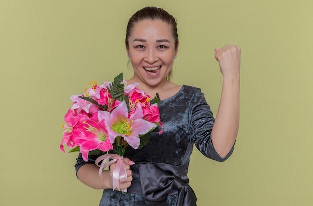 Mulher asiática feliz e animada segurando um buquê de flores com os punhos cerrados e sorrindo alegremente, comemorando o dia internacional da mulher em pé sobre a parede verde