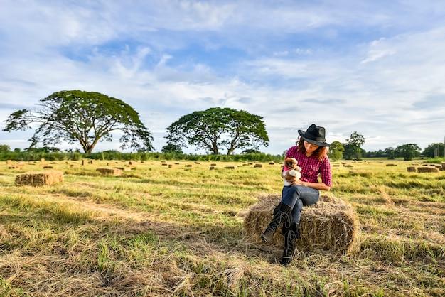 Mulher asiática feliz e jogando seu cachorro no jardim