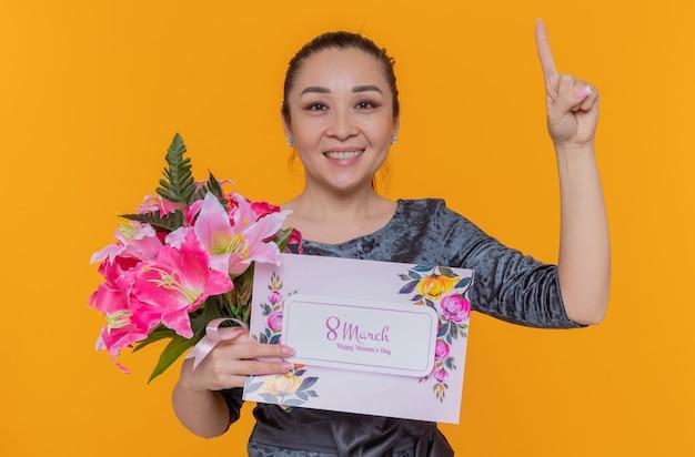 Mulher asiática feliz e positiva segurando um buquê de flores e um cartão comemorando o dia internacional da mulher.