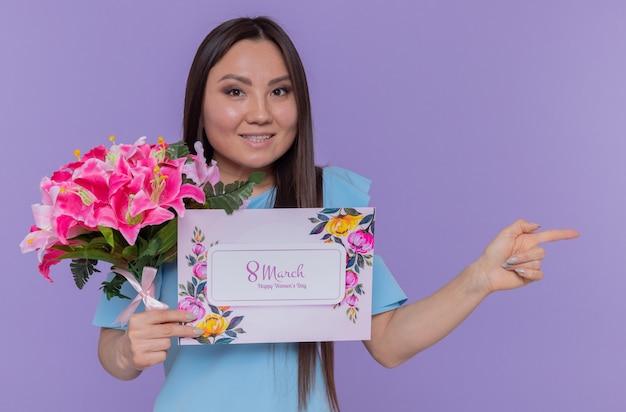 Mulher asiática feliz e positiva segurando um cartão e um buquê de flores