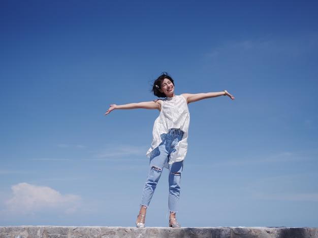 Mulher asiática feliz e sorrir na praia e céu azul