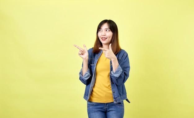 Mulher asiática feliz em jaqueta jeans apontando para cima para copiar o espaço e olhando para a câmera sobre o espaço amarelo