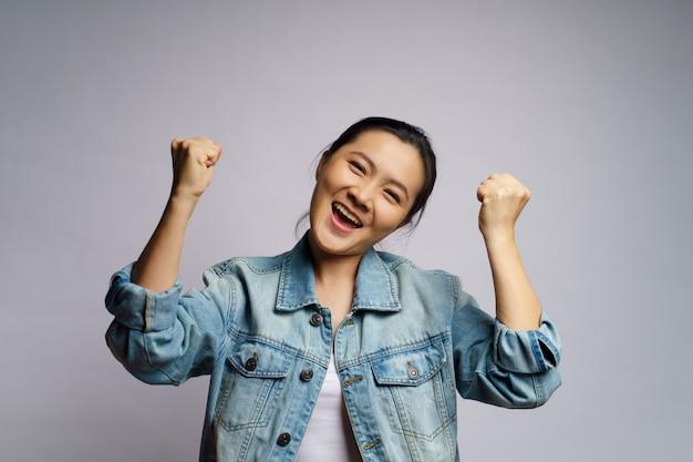 Mulher asiática feliz em pé confiante mostrando o punho faz um gesto vencedor isolado.