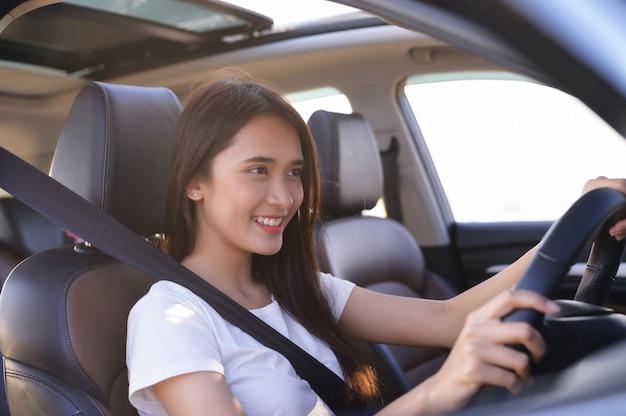 Mulher asiática feliz em um carro. uma mulher bonita sorriu em seu carro novo. seguro de automóvel