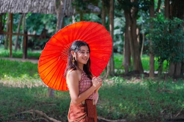 Mulher asiática feliz em um vestido tradicional tailandês com guarda-chuva vermelho, sorrindo enquanto olha a bela vista da natureza em uma floresta de árvores verdes