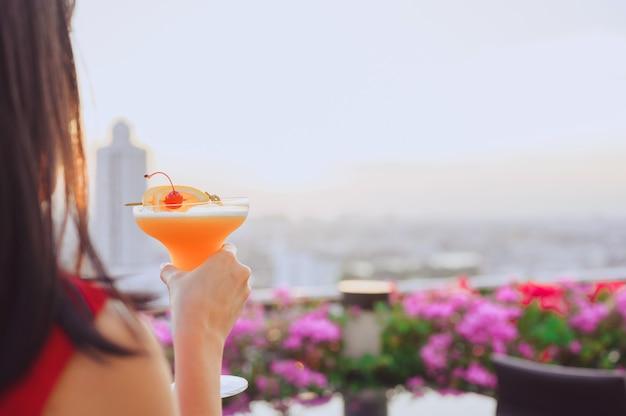 Mulher asiática feliz enquanto bebe um coquetel no restaurante da cobertura