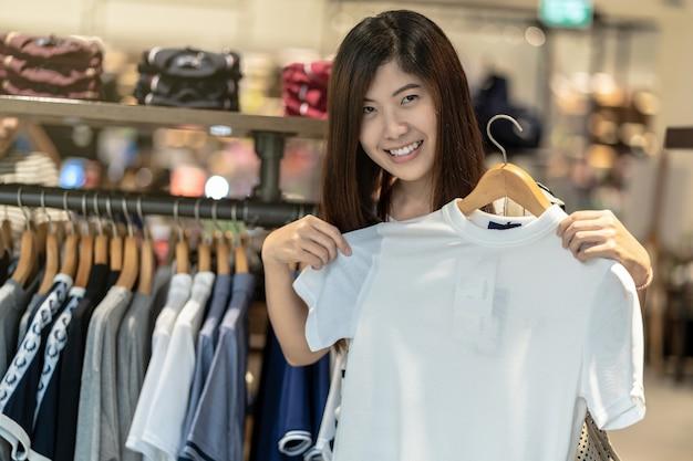 Mulher asiática feliz escolhendo roupas em loja de loja com ação feliz no centro de departamento