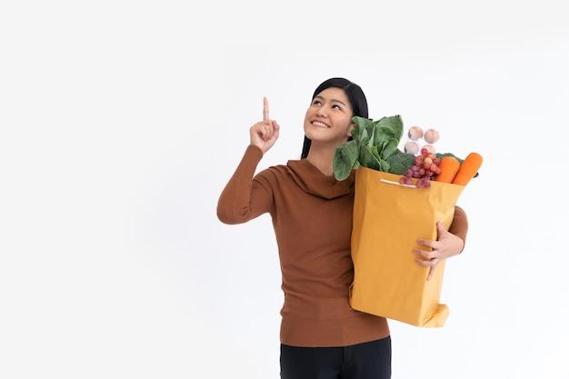 Mulher asiática feliz está sorrindo e com o dedo levantado carregando uma sacola de papel de compras
