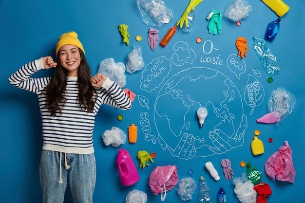 Mulher asiática feliz estende as mãos, fica relaxada e satisfeita, feliz por terminar de limpar o território dos resíduos, posa contra um fundo azul
