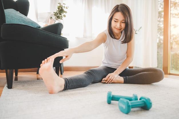 Mulher asiática feliz esticando a perna com halteres no chão em casa na sala de estar
