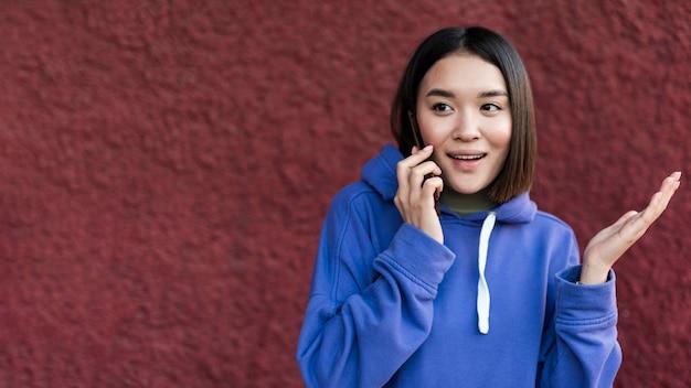 Mulher asiática feliz falando ao telefone