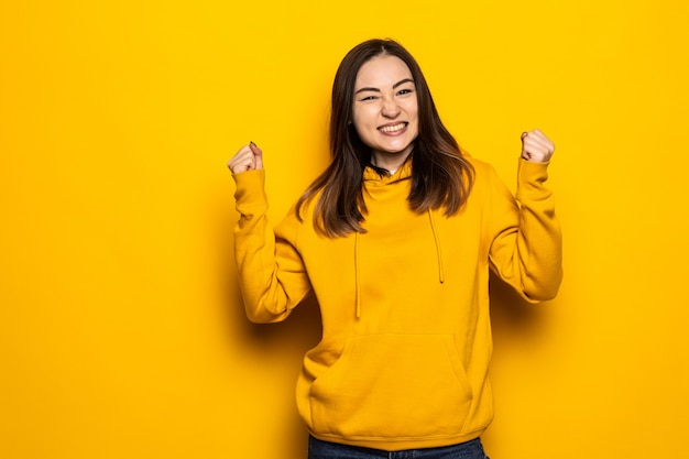 Mulher asiática feliz fazendo gesto vencedor isolado na parede amarela