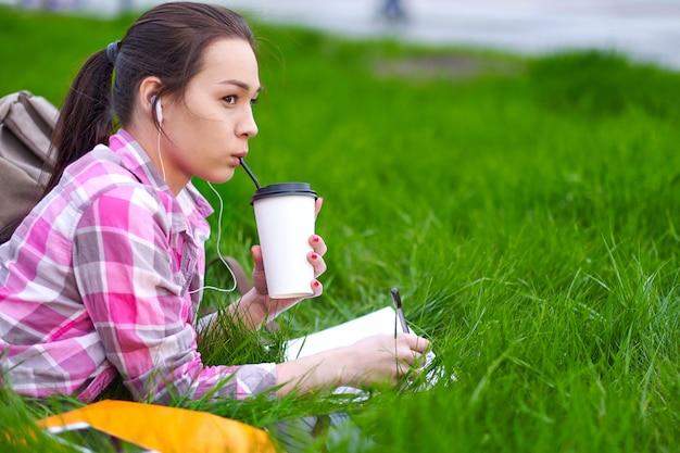 Mulher asiática feliz hipster deitado na grama, sorrindo e segurando uma xícara de café no prado
