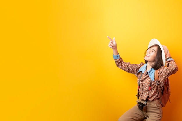 Mulher asiática feliz jovem turista na parede amarela