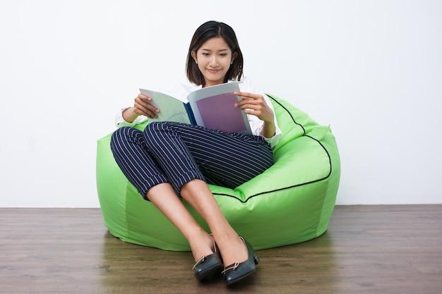 Mulher asiática feliz lendo revista no beanbag