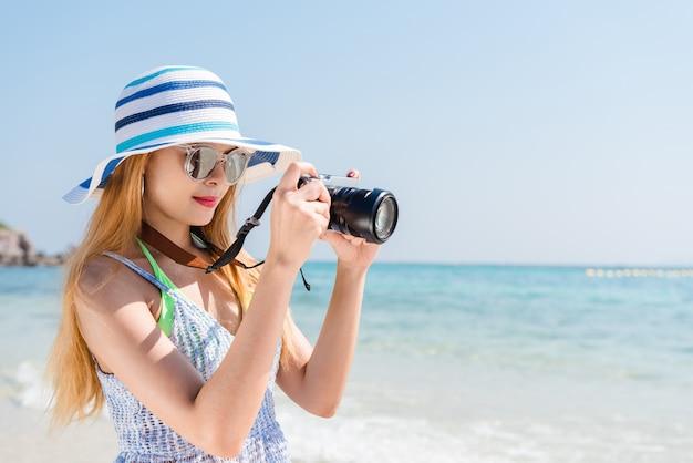 Mulher asiática feliz nas férias fotografando com uma câmera na praia com o horizonte no fundo.