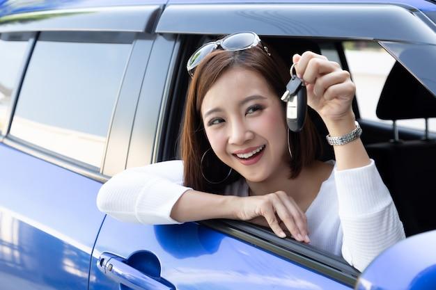 Mulher asiática feliz nova do motorista que sorri e que mostra chaves novas do carro. conceito de drivers iniciantes