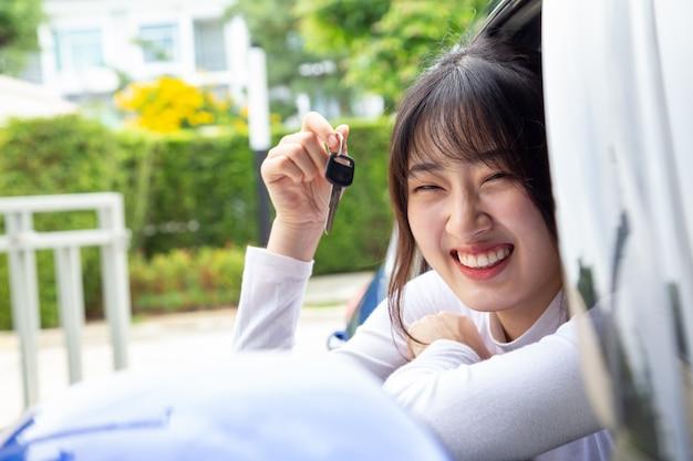 Mulher asiática feliz nova do motorista que sorri e que mostra chaves novas do carro.