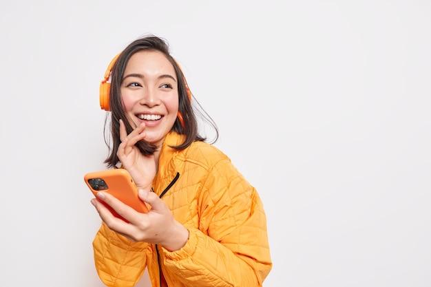 Mulher asiática feliz, positiva, curtindo música, usa fones de ouvido sem fio, segura smartphones, afasta-se, aproveita o tempo livre, desfruta da música vestida com jaqueta laranja posa espaço interno