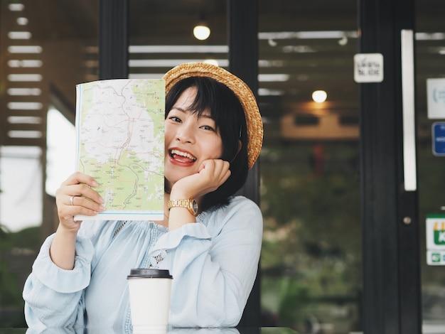Mulher asiática feliz que guarda o mapa nas mãos na cafetaria.