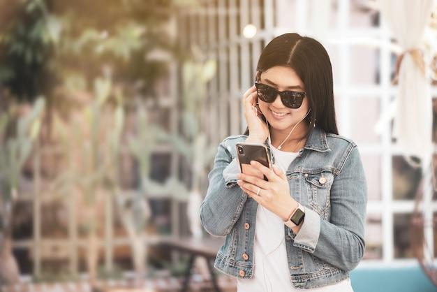 Mulher asiática feliz que usa o telefone para escutar uma música.