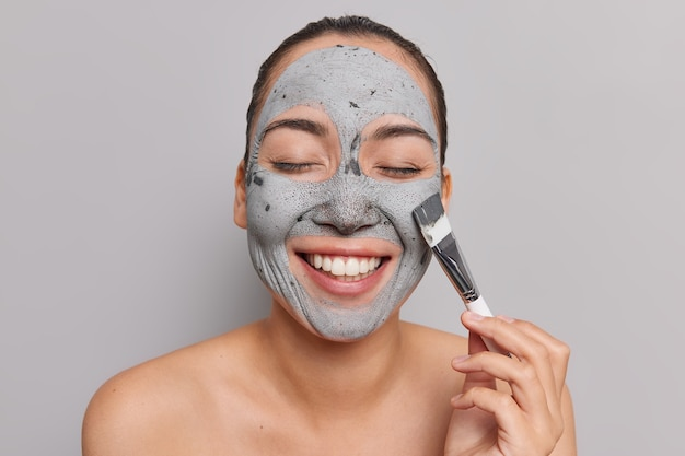 Mulher asiática feliz recebe máscara cosmética e usa sorrisos de escova amplamente
