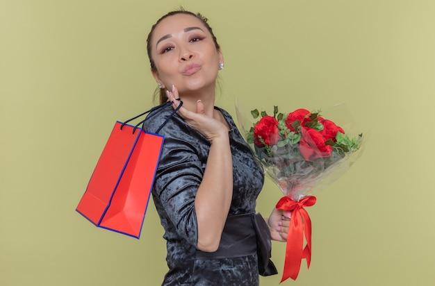 Mulher asiática feliz segurando um buquê de rosas vermelhas e um saco de papel com um presente mandando um beijo para comemorar o dia internacional da mulher em pé sobre a parede verde