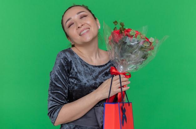 Mulher asiática feliz segurando um buquê de rosas vermelhas e um saco de papel com um presente sorrindo alegremente, comemorando o dia internacional da mulher em pé sobre a parede verde