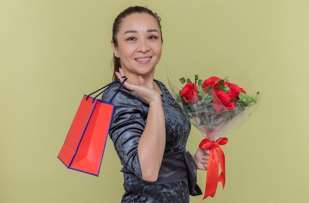 Mulher asiática feliz segurando um buquê de rosas vermelhas e um saco de papel com um presente sorrindo alegremente, olhando para a frente, comemorando o dia internacional da mulher em pé sobre a parede verde