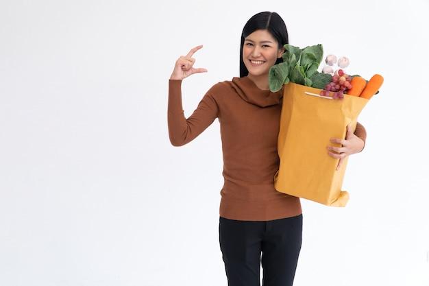 Mulher asiática feliz sorrindo, abrindo a palma da mão e carregando uma sacola de compras