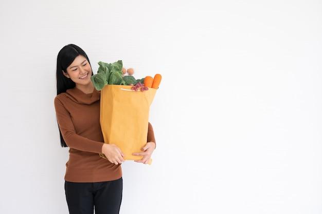 Mulher asiática feliz sorrindo e carregando uma sacola de papel de compras