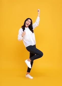 Mulher asiática feliz sorrindo e em pé com a mão celebrando o gesto em amarelo.