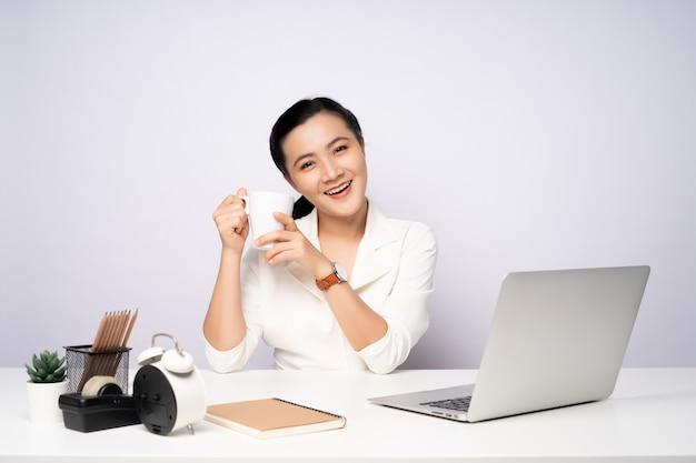 Mulher asiática feliz sorrindo, faça uma pausa depois de trabalhar em um laptop. isolado no fundo branco.