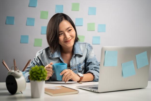 Mulher asiática feliz sorrindo, olhando para o laptop e lendo notícias no escritório em casa. trabalho a partir de casa. conceito de prevenção do coronavirus covid-19.