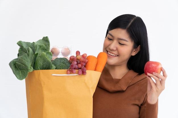 Mulher asiática feliz sorrindo, segurando uma maçã e carregando uma sacola de papel de compras