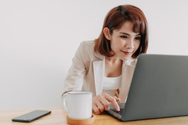 Mulher asiática feliz trabalhando em seu laptop no escritório