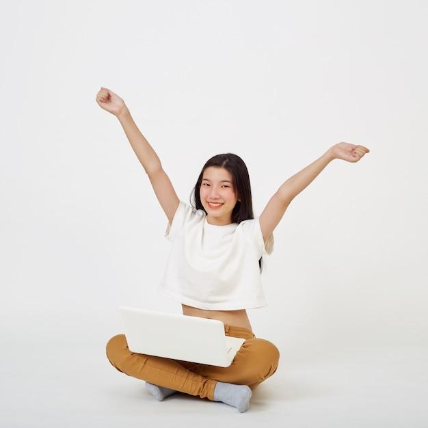 Mulher asiática feliz trabalhando em um laptop sentado no chão com as pernas cruzadas isoladas sobre um fundo branco, conceito de volta à escola