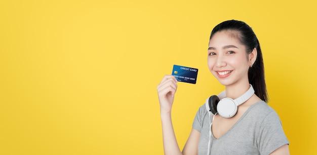 Mulher asiática feliz usando fones de ouvido no pescoço e segurando o pagamento com cartão de crédito.