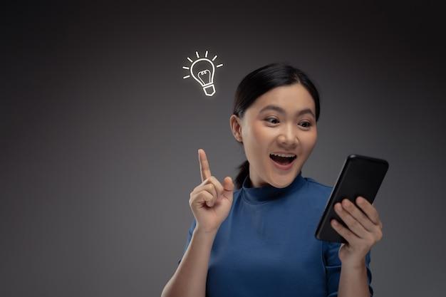 Mulher asiática feliz usando smartphone e efeito de holograma de ícone