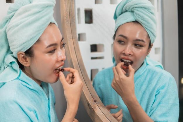 Mulher asiática feliz usando toalha come pílula com vitamina e para nutrição e pele saudável em frente ao espelho