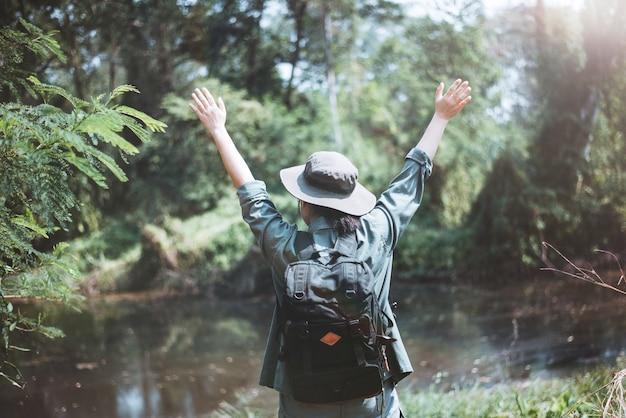 Mulher asiática feliz viajando na floresta, férias de verão ao ar livre