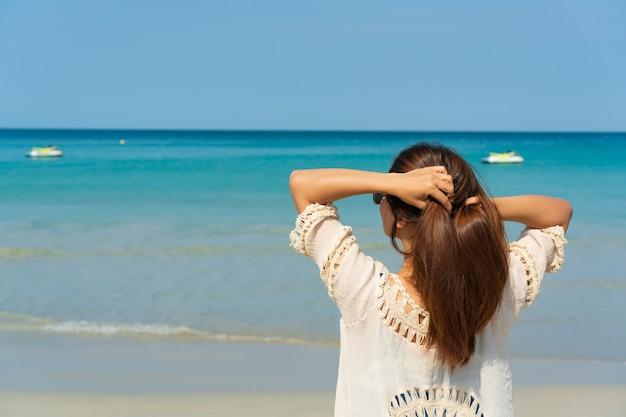 Mulher asiática feliz viajante desfrutar na praia tropical de férias. verão no conceito de praia.