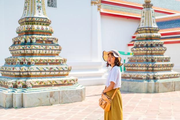 Mulher asiática feliz visitando o templo