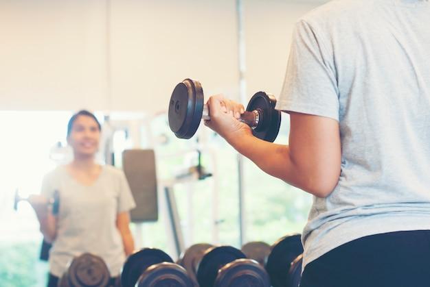 Mulher asiática fitness fazendo levantamento de peso para o exercício no ginásio