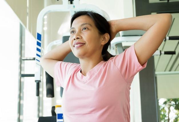 Mulher asiática fitness warm up antes de fazer exercício no ginásio, idade média feminino malhando yoga