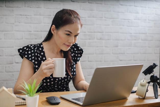 Mulher asiática focada usando o laptop em casa, olhando para a tela, conversando, lendo ou escrevendo e-mail.