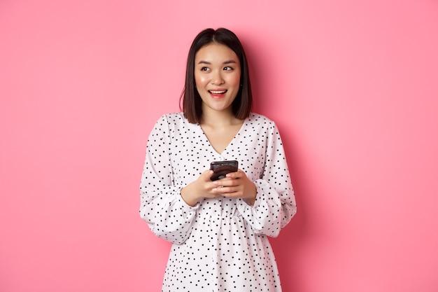 Mulher asiática fofa pensando e sorrindo, parecendo sonhadora enquanto envia uma mensagem no smartphone, navegando em lojas online, em pé sobre um fundo rosa