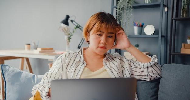 Mulher asiática freelance sente dor de cabeça enquanto está sentada no sofá com um laptop online, aprende na sala de estar de casa